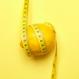 Citron avec la bande de mesure sur un fond jaune Photographie stock