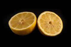Citron coupé dans la moitié sur le fond noir Photographie stock