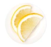 Citron coupé en tranches d'un plat en céramique d'isolement sur le fond blanc, Cl Photo libre de droits