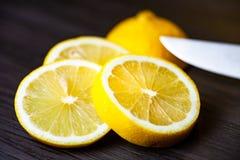 Citron coupé en tranches sur la fin foncée de fond  photographie stock libre de droits