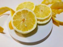 Citron et écorce de citron découpée en tranches d'un plat sur la table blanche grande Photographie stock libre de droits