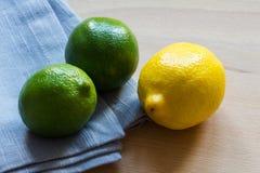 Citron et chaux avec le tissu gris sur le fond en bois Photographie stock libre de droits