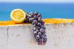Citron et groupe de raisins bleus sur le mur Photographie stock