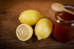 Citron et miel sur une table en bois Photographie stock libre de droits