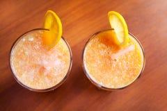 Citron et smoothies oranges sur la table avec des tranches de citron et d'orange dans des tasses en verre avec des tubes Photos libres de droits