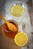 Citron frais avec du miel et le verre de l'eau avec la tranche de citron Photographie stock