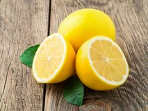 Citron frais et moitié découpée sur la vieille table en bois, vue de côté photo libre de droits