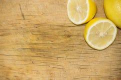 Citron frais jaune et moitié deux de citron sur la planche à découper en bois Photo libre de droits
