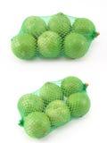 Citron i gröna plast- Mesh Sack på vit bakgrund royaltyfri foto