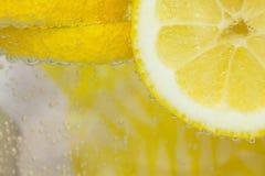 Citron i vatten med bubblor Fotografering för Bildbyråer