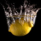 Citron i vatten på en svart bakgrund royaltyfri foto