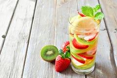Citron jordgubbe, kiwidetoxvatten mot lantligt trä royaltyfri bild