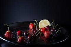 Citron, körsbär och jordgubbar i runt stålmagasin på mörkerbac Royaltyfri Bild