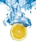 Citron laissé tomber dans une eau Photographie stock