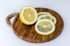Citron och skivor på skärbräda på ljus bakgrund Arkivfoto