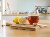 Citron på skärbräda och exponeringsglas av honung royaltyfria foton