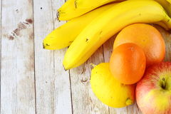 Citron, pamplemousse, banane, pomme et mandarine sur un fond en bois Concept sain de consommation Photos libres de droits