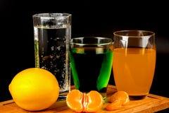 Citron, segments de mandarine et verres avec des boissons Photos libres de droits