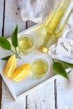 Citron-smaksatt italiensk likör i exponeringsglas Läcker gul alkoholdrink Limoncello starksprit Glasflaska, skott och citrusfrukt arkivfoton