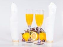 Citron, wineexponeringsglas med fruktsaft och druvor Fotografering för Bildbyråer