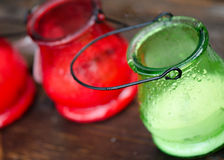 Citronella Candle in the Rain. A shot of red and green candles in the rain during a camping trip to keep bugs away Stock Photography