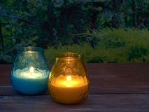 Citronella candles. Blue and yellow citronella candles lit in the garden are being used to keep mosquitoes at bay in late evening Stock Photos