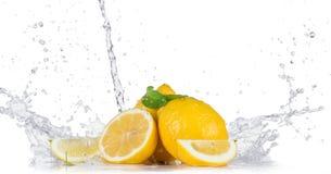 Citronen med bevattnar färgstänk Arkivbilder