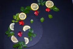 Citronen som skivades i cirklar och halvor, lade ut i form av ett guld- avsnitt eller en spiral arkivfoto