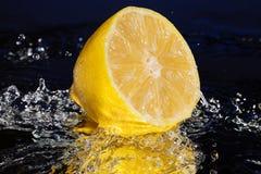 Citronen under vatten med en stor färgstänk på blått avspeglar bakgrund Arkivbild