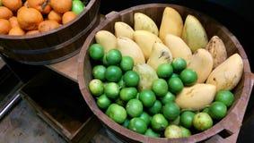 Citroner, mango och apelsiner i trähandfat Arkivfoto