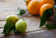 Citroner med apelsiner på tabellen Arkivbild