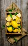 Citroner med sidor i en ask på tyget På träbakgrund arkivbild
