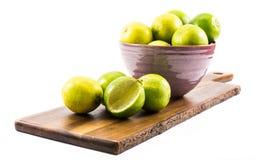 Citroner och limefrukter komponerade i en violett kopp, träbräde, på en vit bakgrund - sidosikt royaltyfri bild