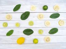 Citroner och limefrukter med gröna blad på trä arkivbilder