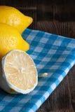 Citroner på den blåa och vita rutiga torkduken royaltyfria foton