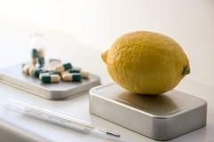 Citroner STÄNGER SIG UPP PÅ den BAKGRUNDSpreventivpillerarna och termometern Fotografering för Bildbyråer