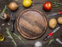 Citroner tomater, lökar, potatisar, rosmarin, kniv för skalning av potatisar som läggas runt om rund skärbrädaställetext, fram Royaltyfri Bild