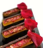 Citrongelé- och chokladefterrätter med nya ätliga rosa kronblad royaltyfria foton