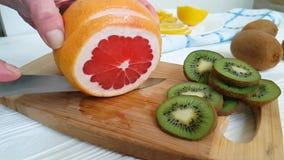 Citrongrapefrukten är huggen av friskhet på en träbrädeförberedelse arkivfilmer
