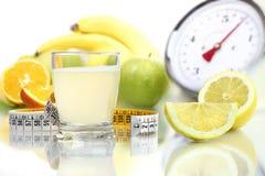 Citronjuice hällt in exponeringsglas, fruktmetervåg bantar mat Royaltyfri Foto