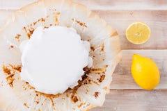 Citronkaka med vit isläggning och nya citroner Arkivfoto