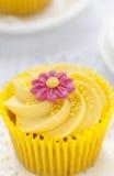 Citronmuffin med smörkrämvirvel och fondanten blommar garnering Arkivbilder