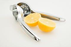 Citronpress med en citron som klipps i halva royaltyfri foto