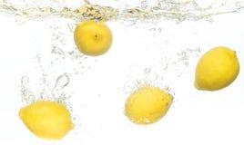 Citrons éclaboussant dans l'eau Photo stock