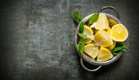 Citrons coupés en tranches frais avec des feuilles dans une casserole Image libre de droits