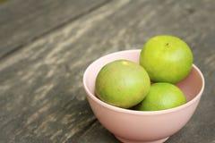 Citrons dans une cuvette rose sur un fond en bois Images stock