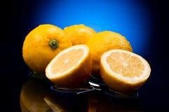 Citrons entiers frais et moitiés Photographie stock