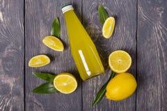 Citrons et bouteille juteux jaunes de jus de citron sur le fond gris photo stock