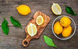 Citrons et feuilles frais de citrons sur le fond en bois rustique Fre Photo stock
