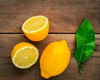Citrons et feuilles frais de citrons sur le fond en bois rustique Fre Photographie stock libre de droits